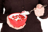Young woman is eating cottage cheese with sliced strawberries — Stock Photo