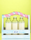 Milk in bottles in wooden box on green background — Foto Stock