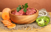 Raw beef meat in bowl with vegetables on wooden table on brown background — Stock Photo