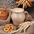 Stock Photo: Jar of milk, tasty bagels and spikelets on wooden background