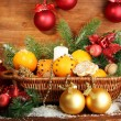Royalty-Free Stock Photo: Christmas composition in basket with oranges and fir tree, on wooden background