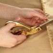Seamstress cut gold fabric close-up — Stock Photo #18604251