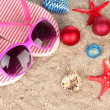 Christmas balls,seashells andh beach accessories on sand, close-up — Photo