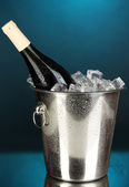 Bottle of wine in ice bucket on darck blue background — Stock Photo