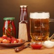 Beer and grilled sausages on wooden table on brown background — Stock Photo