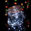 Christmas lights in glass bottle on blur lights background - Stock Photo