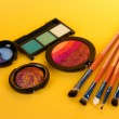 Eye shadows and brushes on yellow background - Stock Photo