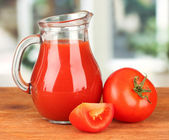 Full jug of tomato juice, on wooden table on bright background — Stok fotoğraf
