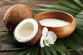Noix de coco avec feuilles et fleurs, sur fond en bois gris — Photo