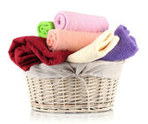 Colorful towels in basket isolated on white — Stock Photo