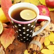 Stock Photo: Cup of hot teand autumn leaves, on wooden background