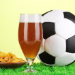 Glass of beer with soccer ball on grass on green background — Stock Photo #18658743