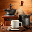 Coffee grinder, turk and cup of coffee on brown wooden background — Stockfoto