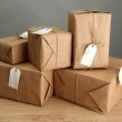 Parcels boxes with kraft paper, on wooden table on grey background — Stock Photo #18659031