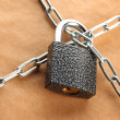 Foto Stock: Parcel with chain and padlock, close up