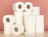 Rolls of toilet paper on striped red background — Stock Photo