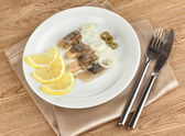 Dish of herring and lemon on plate on wooden table close-up — Stock Photo