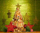 Beautiful christmas tree of dry lemons with decor, on shine green background — Stock Photo