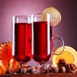 Mulled wine in the glasses, spice and orange on wooden table on purple background — Foto Stock
