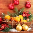 Christmas composition in basket with oranges and fir tree, on wooden background — Stock Photo #18664181