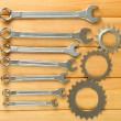 Metal cogwheels and spanners on wooden background — ストック写真