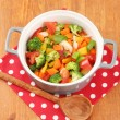 Vegetable stew in gray pot on color napkin on wooden background - Stock Photo