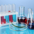Test-tubes and green leaf tested in petri dish, on color background — Stock Photo #18664669