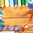 Sewing accessories and fabric on wooden table close-up — Stock Photo #18665315