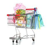 Carrinho de compras com presentes brilhantes e sacos de papel isolados no branco — Fotografia Stock