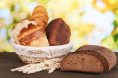 Fresh bread in basket on wooden table on natural background — Stock Photo