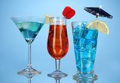 Alcoholic cocktails with ice on blue background — Stock Photo