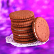 Chocolate cookies with creamy layer on purple background - Photo