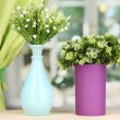 Decorative flowers in vases on windowsill — Stock Photo #18697439