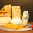 Stock Photo: Various types of cheese on wooden table on brown background