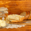 Butter on glass saucer with glass cover and fresh bread, honey on wooden background — Stock Photo