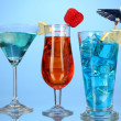 Alcoholic cocktails with ice on blue background - Stock Photo