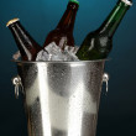 Beer bottles in ice bucket on darck blue background — Stock Photo