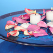 Rose petals and candles in water in vase on blue background close-up - Stock Photo