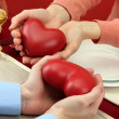 Hands of romantic couple with hearts over a restaurant table — Stock Photo #18698435
