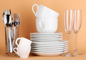 Clean white dishes on beige background — Stock Photo