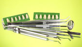 Set of dental tools with denture on green background — Stock Photo