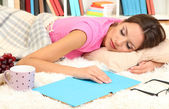 Young female asleep while reading book on floor — Stock Photo