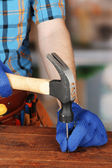 Builder's hands hammering nail into wood — Stock Photo