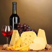 各种类型的棕色背景上的木桌上的奶酪 — 图库照片