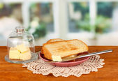 Butter on glass saucer with glass cover surrounded by bread, on bright background — Stock Photo