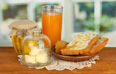 Butter on glass saucer with glass cover and fresh bread,honey, on bright background — Stock Photo