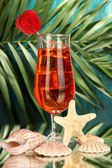 Alcoholic fruit cocktail with ice on tropical background — Stock Photo