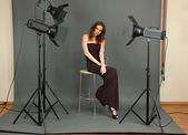 Beautiful professional female model resting between shots in photography studio shoot set-up — Stock Photo