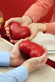Hands of romantic couple with hearts over a restaurant table — Stock Photo