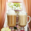 Fragrant coffee latte in glasses cups with vanilla pods, on table in cafe — Стоковая фотография